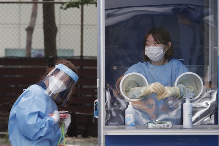 A medical worker holds a portable fan during the sweltering heat at a makeshift clinic at the Seoul Metropolitan Police Agency in Seoul, Wednesday, Aug. 19, 2020. AP