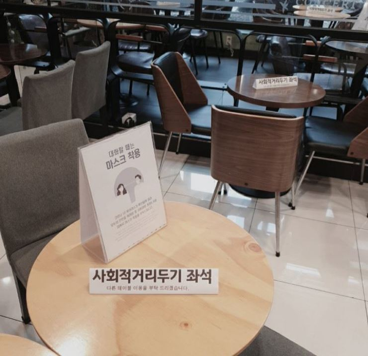 'Don't sit' signs on tables at a cafe in Seoul, Sunday. Under an enhanced social distancing rule, imposed on Seoul and surrounding areas from Sunday, coffee shops are allowed to take orders for takeout or delivery. Korea Times photo by Park Si-soo