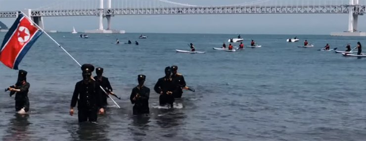 Seven university students in North Korean military uniforms are seen in the farcical Operation Busan Landing performance on Busan's Gwangan Beach in July last year in this image capture.