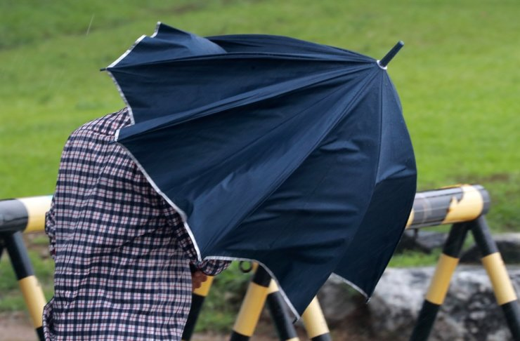 A man shelters from gusts near Haeundae Beach in Busan, Monday. Yonhap