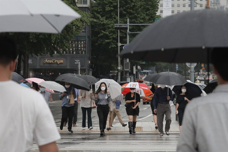 People wearing face masks to help protect against the spread of the new coronavirus cross a road in Seoul, Monday, Aug. 3, 2020. AP