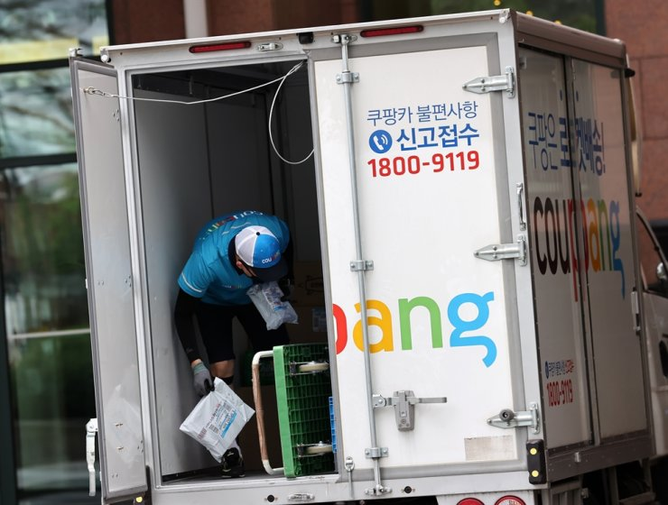 A Coupang employee is busy with parcels to deliver in Seoul's Jongno-gu District, Friday. Yonhap