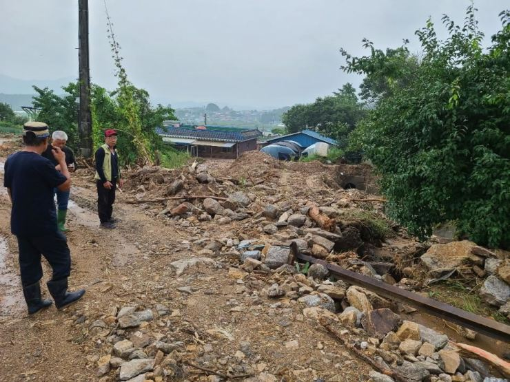 Residents in Eumseong, North Chungcheong Province, look around their village, Tuesday, after the heavy rains pouring down since Saturday triggered a string of mudslides and flooding. / Yonhap