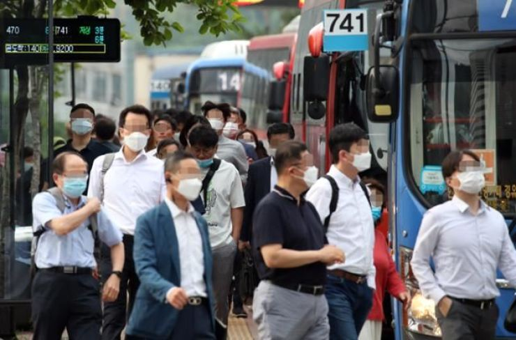 People wear face masks at a bus stop on Aug. 18 in Seoul. / Korea Times photo by Lim Hyun-jeong