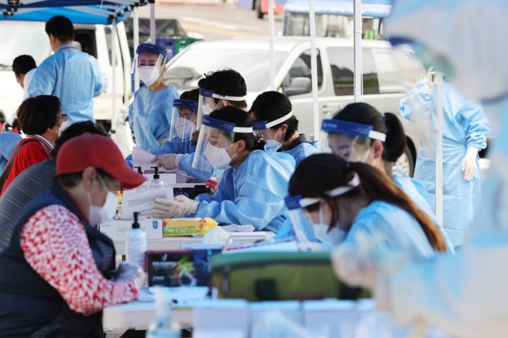 Health officials carry out COVID-19 testing on citizens at a makeshift facility erected in Namdaemun Market, central Seoul, Monday, following an outbreak of infections at the marketplace. / Yonhap