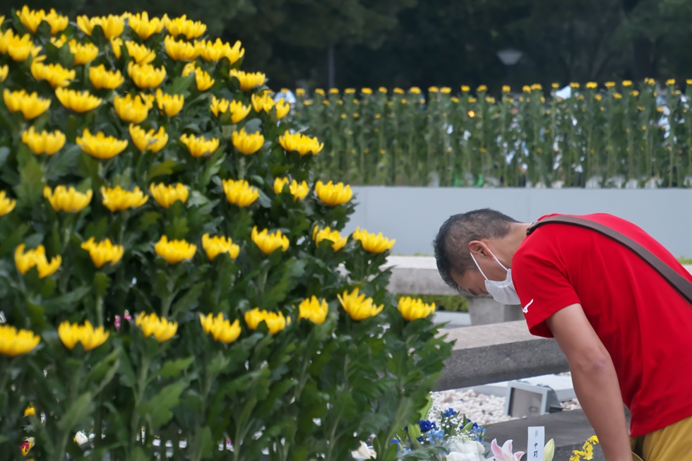 Miki Fukui observes five minutes of silence during a vigil at Park Square in Pittsfield, Mass., Thursday, Aug. 6, 2020, on the 75th anniversary of the day the U.S. dropped an atomic bomb on Hiroshima, Japan, killing over 100,000 people. At 8:15 a.m., the time that the bomb fissioned above Hiroshima in 1945, the gathered participants held five minutes of silence in remembrance. (Stephanie Zollshan/The Berkshire Eagle via AP)