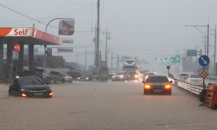 Cars stranded on a flooded road in Yongin, Gyeonggi Province, Sunday. / Yonhap
