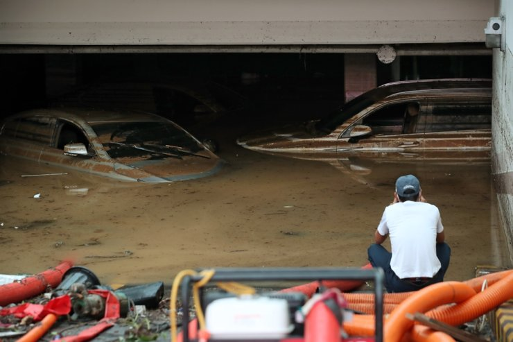 A man stares at the vehicles submerged in floodwaters at a Gwangju parking lot, South Jeolla Province, Sunday. Yonhap