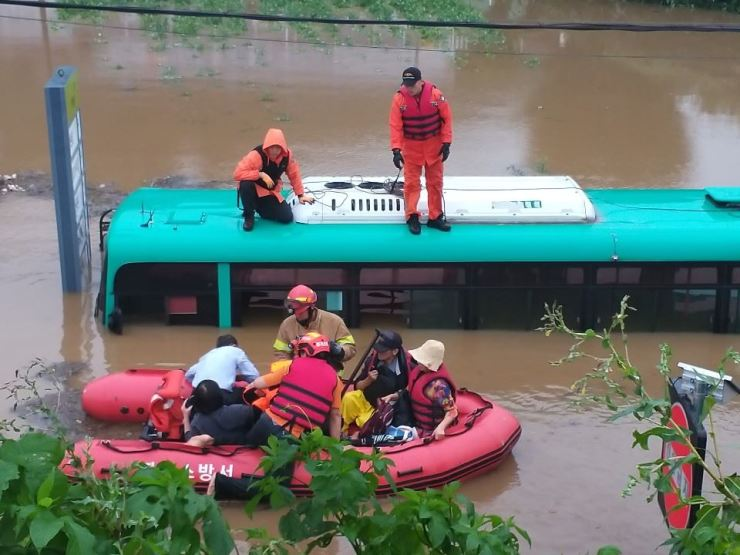 Disaster relief workers rescue passengers in Paju, Gyeonggi Province, Thursday, after a bus was submerged in floodwaters caused by torrential rain that has continued to hit the nation's interior since Saturday. / Yonhap