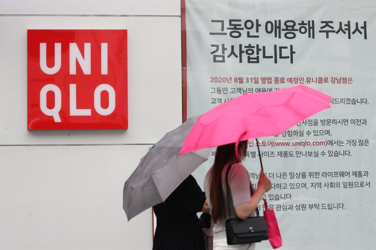 People walk pass by a notice on the wall of a Uniqlo store in Gangnam, southern Seoul, explaining that the store will close on Aug. 31, 2020. / Yonhap
