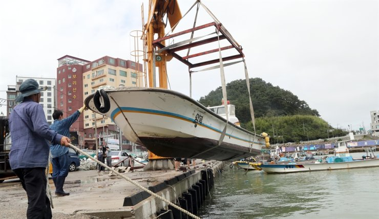 A fishing boat is lifted on to land at a port in Busan on Monday to shelter from typhoon Jangmi. Yonhap
