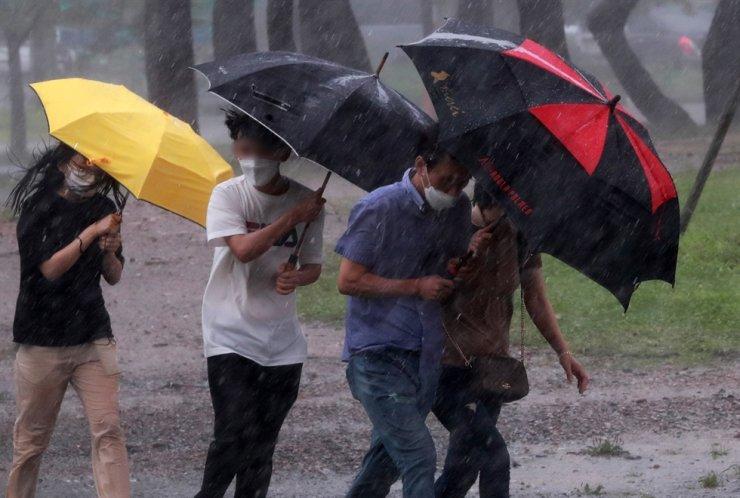 People brave typhoon-driven heavy rain in Busan, Monday. Yonhap