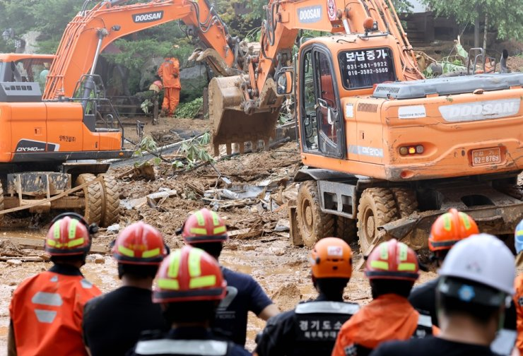 Firefighters search through debris during rescue efforts at the resort area in Gapyeong, Gyeonggi Province, Monday. / Yonhap