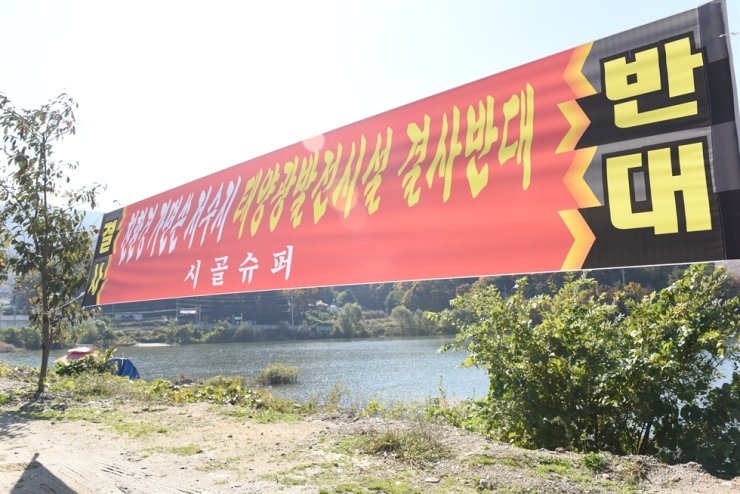 In this October 2018 photo, residents of Seonggeo-eup town in Cheonan, South Chungcheong Province, demand construction of a floating photovoltaic system at the town's reservoir ― led by the Korea Rural Community Corporation ― be shut down. The banner reads: 'We object to PV facility disguised as being eco-friendly.' Korea Times file