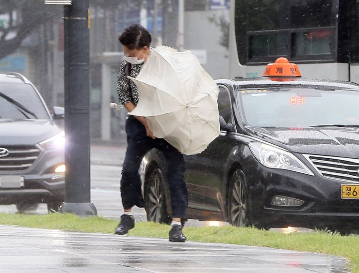 A man barely stands against typhoon-driven wind gusts on Jeju Island, Wednesday. Yonhap