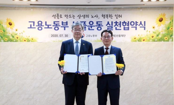 Employment and Labor Minister Lee Jae-kap, left, poses with Sunfull Foundation Chairman Min Byoung-chul after signing a memorandum of understanding at the Seoul Regional Employment and Labor administration, Thursday. Courtesy of Sunfull Foundation