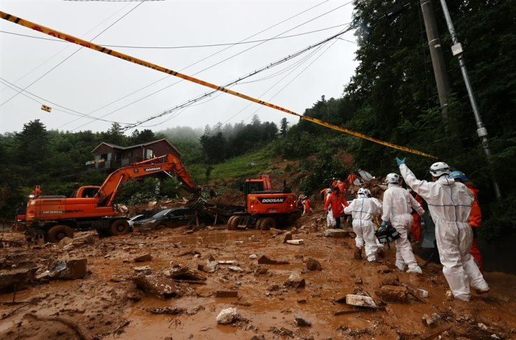 Firefighters search debris during rescue efforts at the resort area in Gapyeong, Gyeonggi Province, Monday. Yonhap