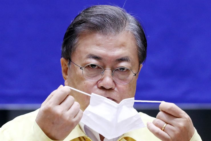 President Moon Jae-in puts on a mask before a meeting at Seoul City Hall, Friday. Yonhap