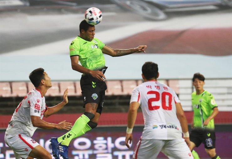 Jeonbuk Hyundai's Brazilian striker Gustavo, second from left, heads the ball during the K League 1 match against Sangju Sangmu at the Jeonju World Cup Stadium, Sunday. / Yonhap
