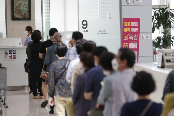 People wait for flu vaccine shots that they opted to pay for at a public medical clinic in Gwangju, Wednesday. Yonhap