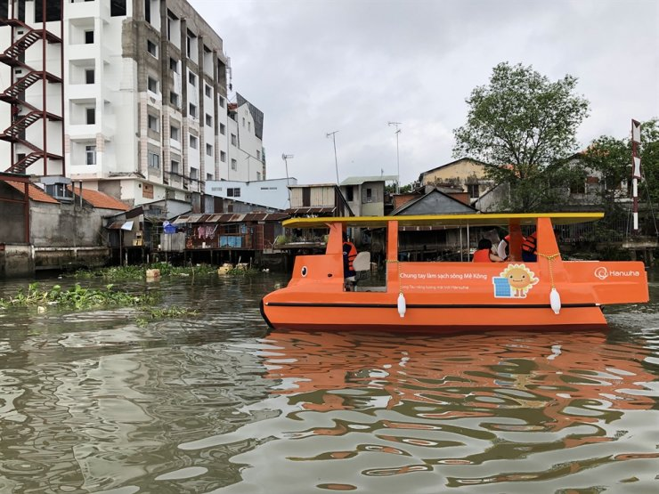 Hanwha's solar-powered boat collects floating garbage from the Mekong River in Vietnam. The campaign 'Solar Boat: Clean Up Mekong' received four awards at the 2020 Superior Achievement in Branding, Reputation & Engagement (SABRE) Awards (Asia-Pacific), which is the world's largest PR program award. Courtesy of Hanwha Group
