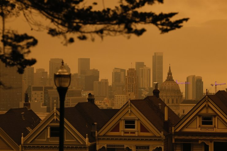 A view of the Painted Ladies, the iconic row of historical Victorian homes with a downtown backdrop, under orange overcast sky in the afternoon in San Francisco, California, USA, 09 September 2020. California wildfire smoke high in the atmosphere over the San Francisco Bay Area blocked the sunlight and turned the sky a dark orange and yellow shade for most of the day. /EPA