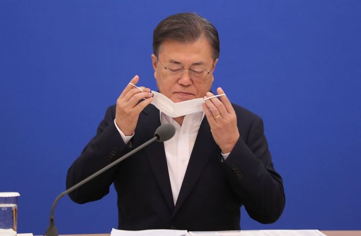 President Moon Jae-in takes off his mask before speaking at the eighth Emergency Economic Council meeting in Cheong Wa Dae, Thursday. Support rates for Moon and the ruling Democratic Party of Korea have dropped largely among young people and men, widely seen as a result of influence-peddling allegations surrounding Justice Minister Choo Mi-ae over her son's military service. Yonhap