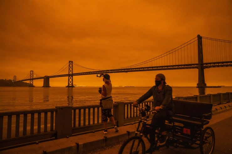 SAN FRANCISCO, CA - SEPTEMBER 09: Amy Scott of San Francisco takes in the view from the Embarcadero as smoke from various wildfires burning across Northern California mixes with the marine layer, blanketing San Francisco in darkness and an orange glow on September 9, 2020 in San Francisco, California. /AFP