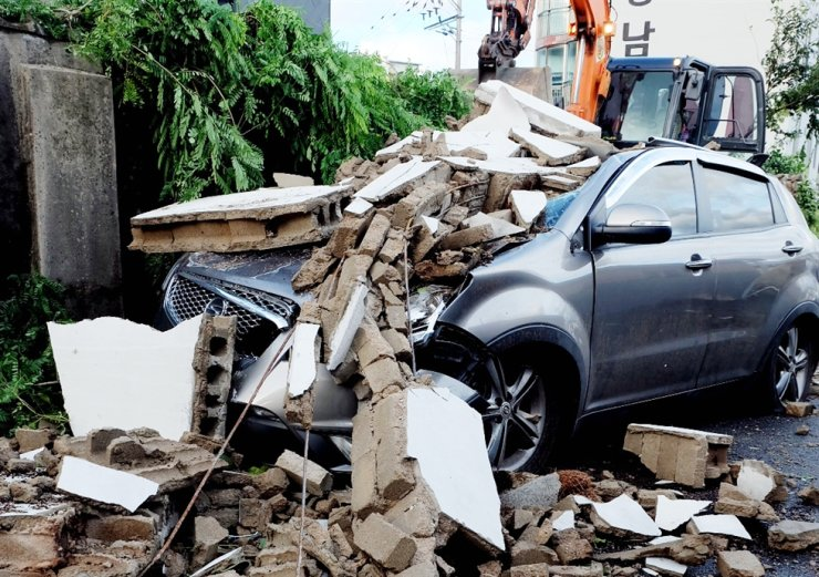A vehicle was destroyed by fallen debris from walls near an unused factory in Ulsan's Buk-gu District on Sept. 3 which crumbled due to an impact from Typhoon Maysak. Yonhap