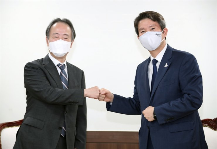 South Korean Unification Minister Lee In-young, right, poses with Japanese Ambassador Koji Tomita at his office in Seoul, Tuesday. Yonhap