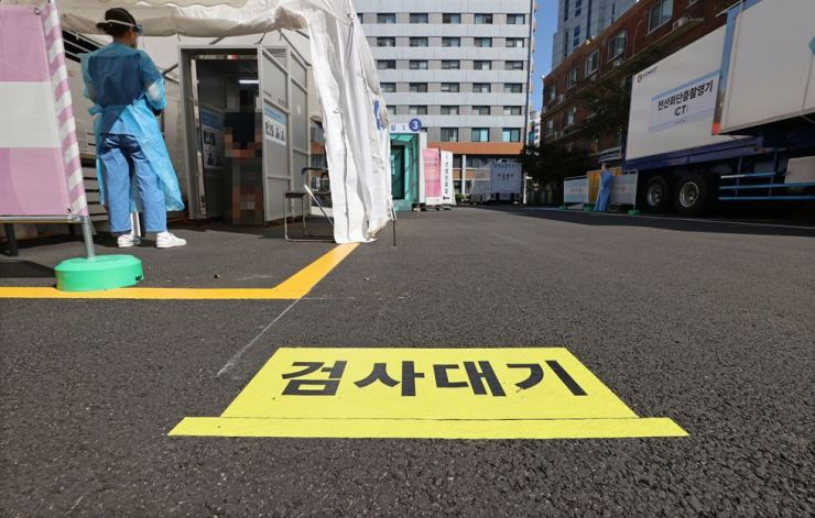 A medical staff member works at a makeshift clinic located in central Seoul, Sunday. Yonhap