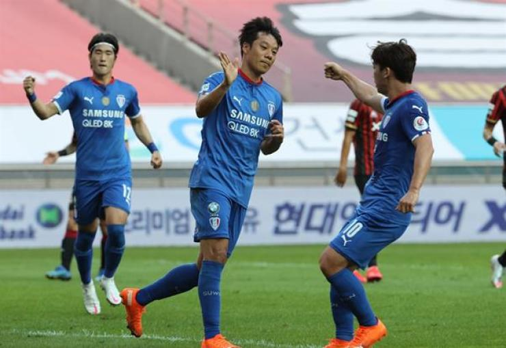 Suwon Samsung Bluewings midfielder Yeom Ki-hun, center, celebrates with his teammates after scoring the penalty kick during the K League 1 match against FC Seoul at the Seoul World Cup Stadium, Sunday. / Yonhap