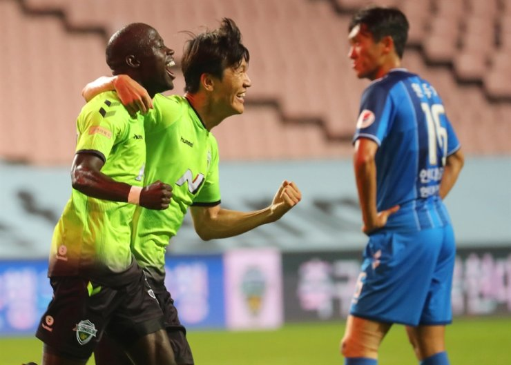 Jeonbuk Hyundai' winger Han Kyo-won, center, celebrates with his teammate Modou Barrow, left, during the K League 1 match against Ulsan Hyundai at Jeonju World Cup Stadium, Tuesday. / Yonhap