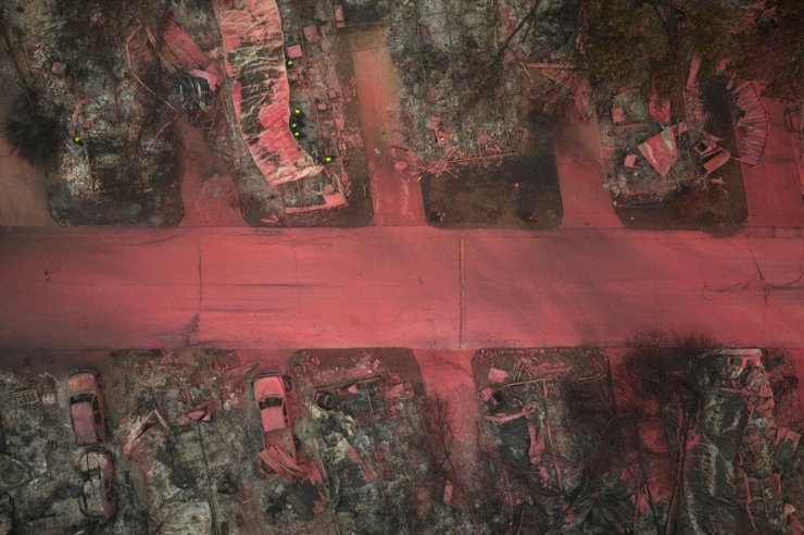 A search and rescue team, surrounded by red fire retardant, look for victims under burned residences and vehicles in the aftermath of the Almeda fire in Talent, Oregon, U.S., September 13, 2020. Picture taken with a drone. /REUTERS