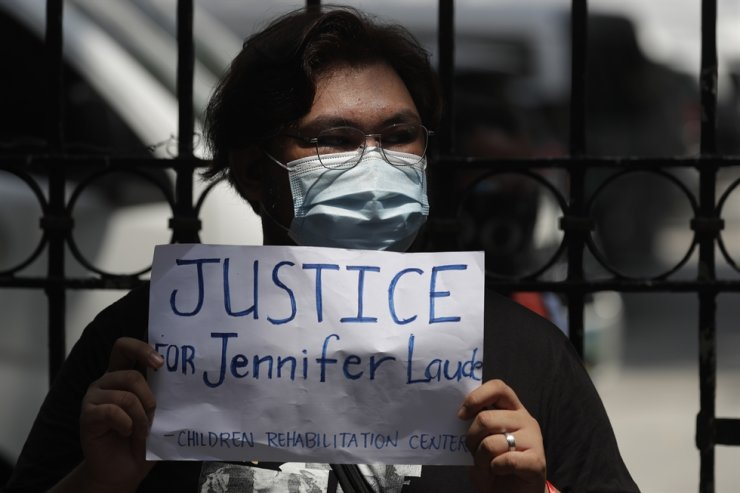 A protester holds a slogan during a rally outside the Department of Justice in Manila, Thursday, Sept. 3, 2020. A Philippine court has ordered the early release for good conduct of U.S. Marine Lance Cpl. Joseph Scott Pemberton convicted in the 2014 killing of transgender Filipino Jennifer Laude, which sparked anger in the former American colony. AP