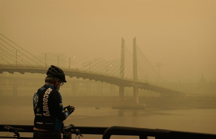 A man stops on his bike along the Willamette River as smoke from wildfires partially obscures the Tilikum Crossing Bridge, Saturday, Sept. 12, 2020, in Portland, Ore. AP-Yonhap