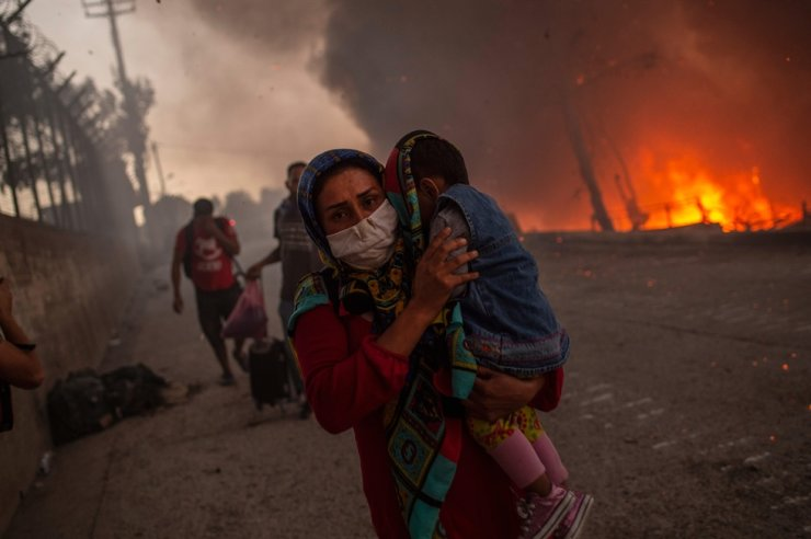 A woman carries a child past flames after a major fire broke out in the Moria migrants camp on the Greek Aegean island of Lesbos, on September 9, 2020. /AFP