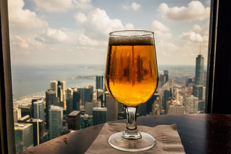 A cup of beer is placed on the table, overlooking Chicago skyline. / Courtesy of Brand USA