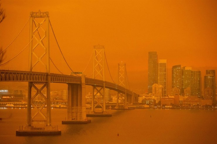 The San Francisco Bay Bridge and city skyline are obscured in orange smoke and haze as their seen from Treasure Island in San Francisco, California on September 9, 2020. - More than 300,000 acres are burning across the northwestern state including 35 major wildfires, with at least five towns 'substantially destroyed' and mass evacuations taking place. /AFP