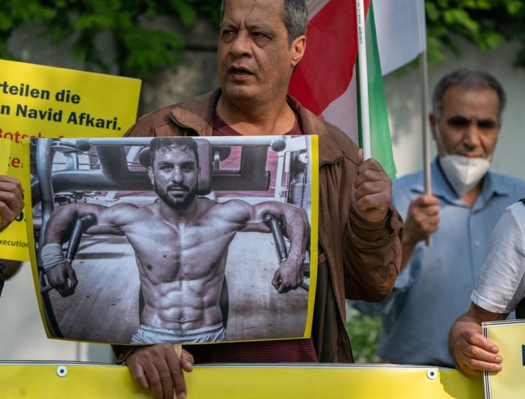 A supporter of the National Council of Resistance Iran (NWRI) and the Iranian Exile Society in Berlin holds a placard with th picture of Iranian wrestler Navid Afkari while protesting against his execution at the Iranian embassy in Berlin, Germany, 12 September 2020. EPA-Yonhap