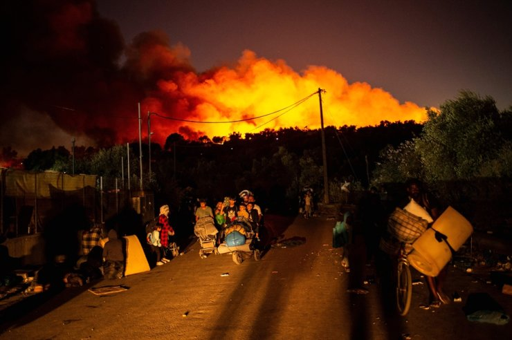 People carrying belongins flee flames after a major fire broke out in the Moria migrants camp on the Greek Aegean island of Lesbos, on September 9, 2020. /AFP