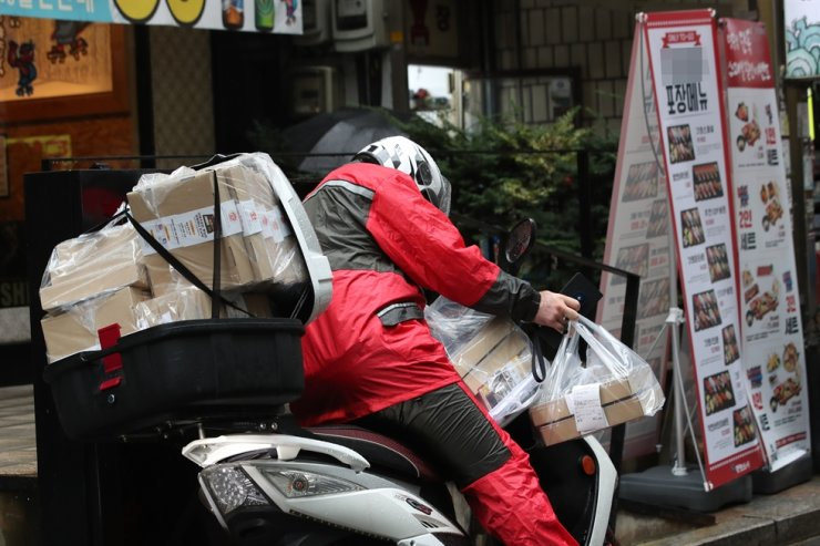 A man gets ready to deliver food in front of a restaurant in Seoul, Sept. 2. Yonhap