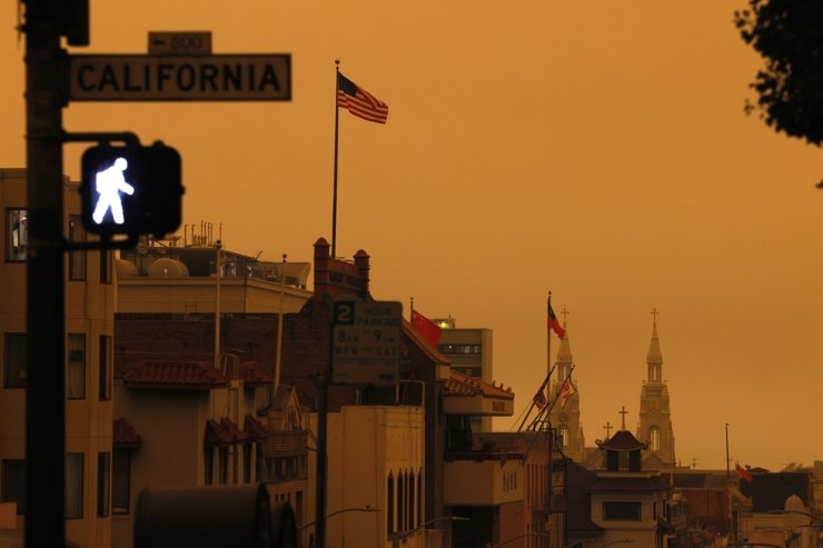 A pedestrian light illuminates a crosswalk on California Street over an orange overcast sky in the afternoon in San Francisco, California, USA, 09 September 2020. California wildfire smoke high in the atmosphere over the San Francisco Bay Area blocked the sunlight and turned the sky a dark orange and yellow shade for most of the day. /EPA