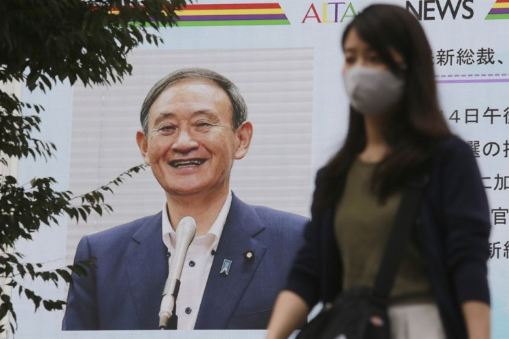 A woman walks by a large screen showing Yoshihide Suga, in Tokyo, Monday, Sept. 14, 2020. AP