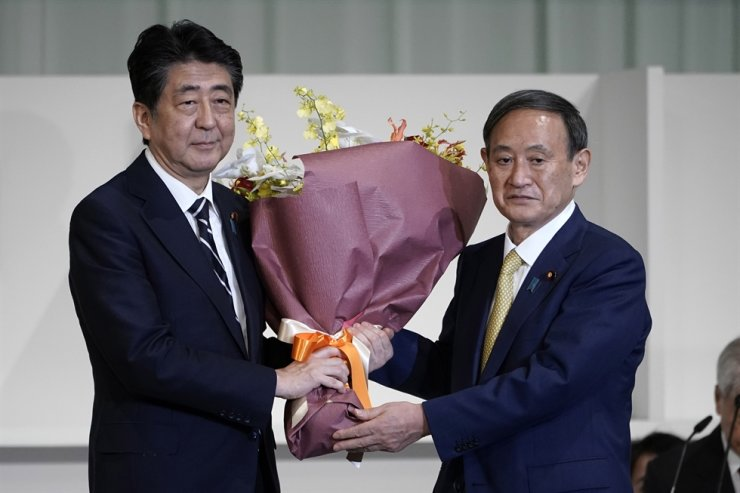 Japan's Prime Minister Shinzo Abe, left, presents Chief Cabinet Secretary Yoshihide Suga flowers after Suga was elected as new head of Japan's ruling party during the Liberal Democratic Party's leadership election in Tokyo, Sept. 14, 2020. EPA