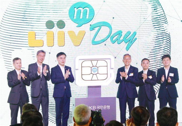 KB Financial Group Chairman Yoon Jong-kyoo, third from right, applauds with KB Kookmin Bank CEO Hur Yin, second from left, and other officials at the bank's launch of Liiv M, a budget phone service at the Banyan Tree Club & Spa, Oct. 28, 2019. First from left is LG Uplus CEO Ha Hyun-hwoi and third from left is Financial Services Commission Vice Chairman Sohn Byung-doo. Courtesy of KB Kookmin Bank