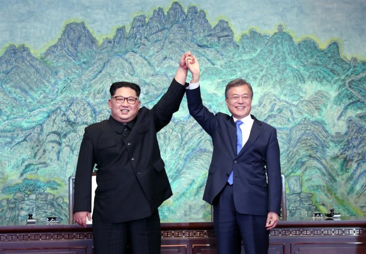 President Moon Jae-in and North Korean leader Kim Jong-un hold hands during their first summit at the truce village of Panmunjeom, April 27, 2018. They held three inter-Korean summits that year, but six South Korean detainees in North Korea have not been released yet. / Korea Times file