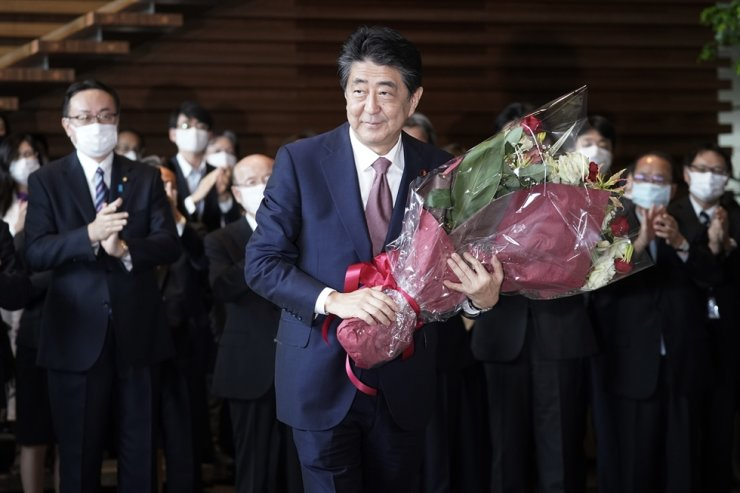 Outgoing Japan's Prime Minister Shinzo Abe receives a bouquet of flowers before leaving the prime minister's office Wednesday, Sept. 16, 2020, in Tokyo. AP