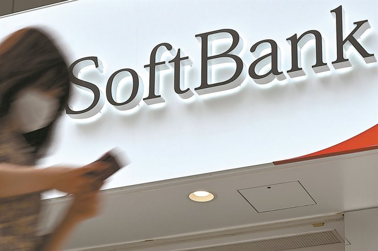 In this file photo taken on June 23, a woman walks past a SoftBank telecommunications store on a street in Tokyo. AFP-Yonhap