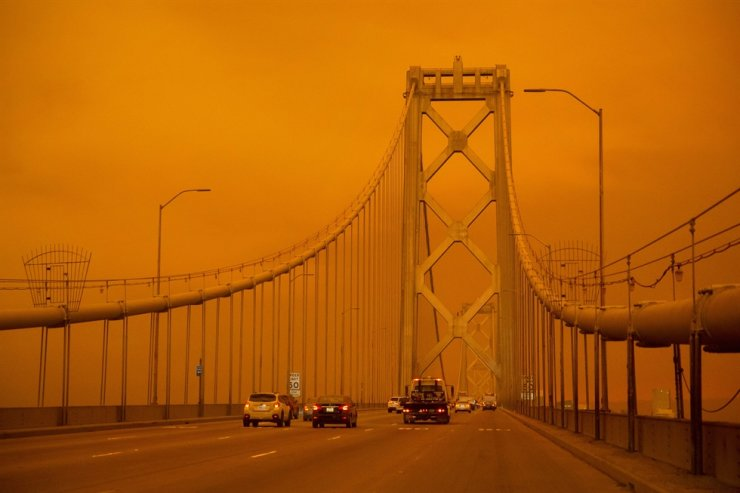 Cars drive along the San Francisco Bay Bridge under an orange smoke filled sky in San Francisco San Francisco, California on September 9, 2020. /AFP